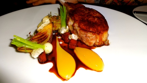 Iberia Pork Chop with Cabbage, Confit Onion, and Apple.