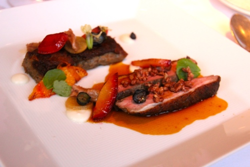 Duck Breast with Smoked Duck Tongue, Blueberries, and Peach Duck Jus.