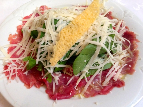Beef Carpaccio with Arugula and Parmigiano Reggiano Cheese.